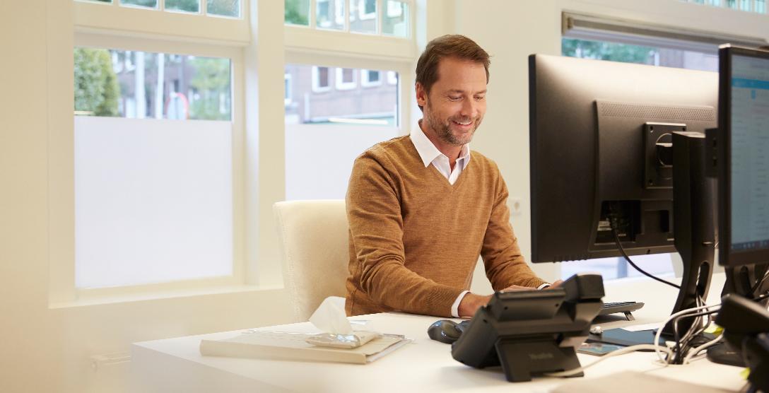 Man met wet wipe achter computer